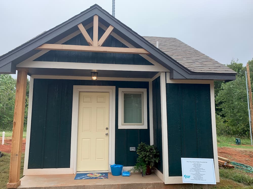 After photo of updated tiny house with blue paint and new Pella windows