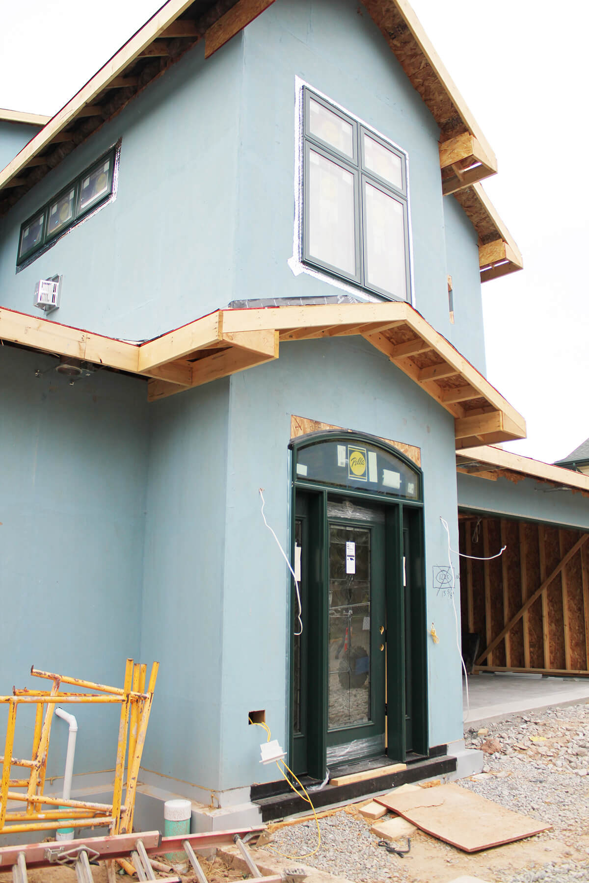 An in progress photo of the homes front, featuring a Pella entryway door and window.