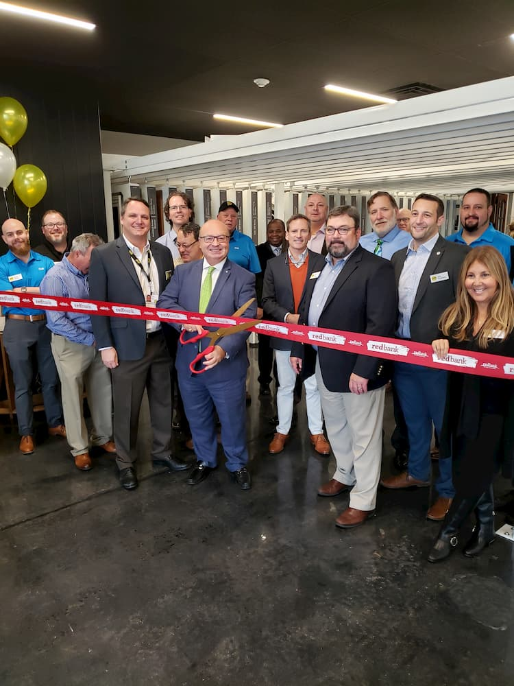 A group of smiling business people cutting the ribbon at the Pella Red Bank Experience Center
