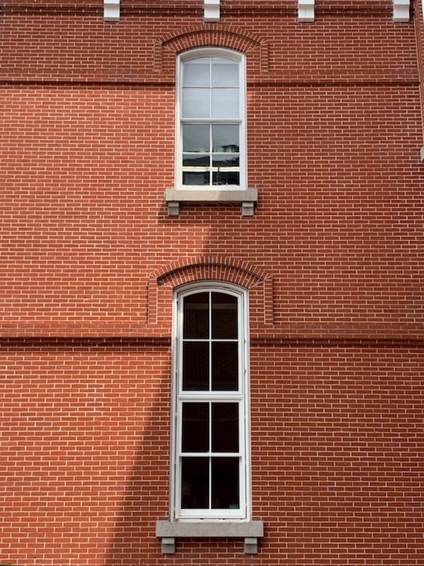 Red brick courthouse building with original windows on top and new Pella wood windows on the bottom