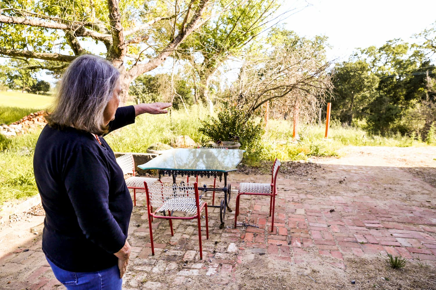 Older woman standing on brick patio surveying backyard