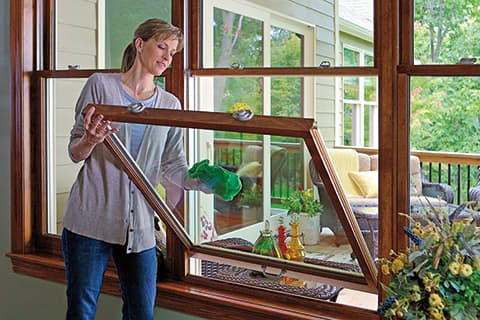 Woman cleaning double-hung windows with cloth