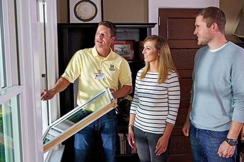 Pella window expert and homeowners inspect window at free in-home consultation