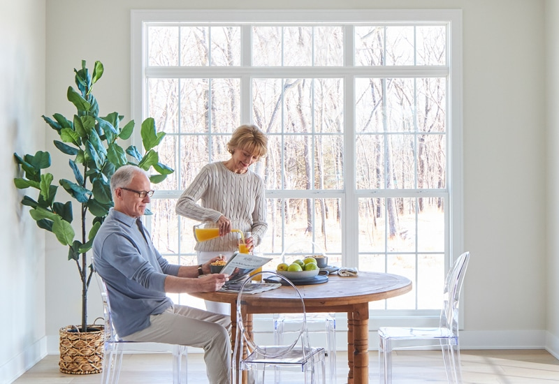 Senior couple having breakfast in front of large windows