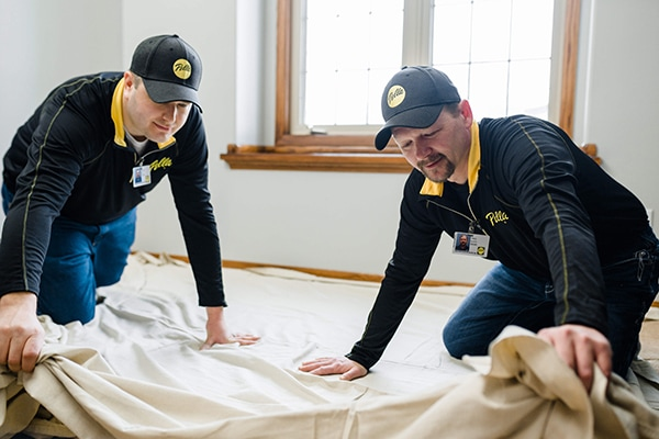 Pella window installers lay down a sheet for easy clean-up after window replacement