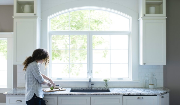 Woman working at kitchen countertop in front of arched window combination