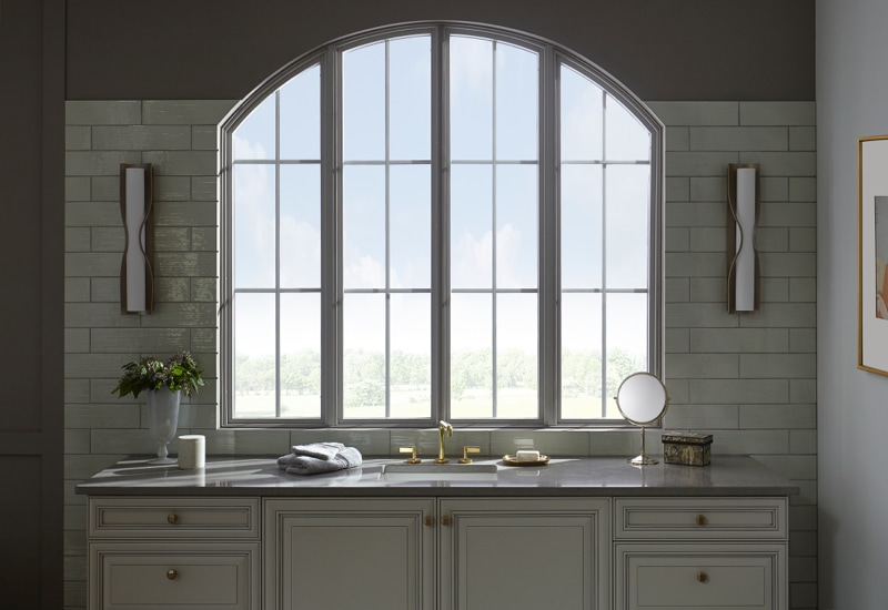 Arched window above bathroom sink