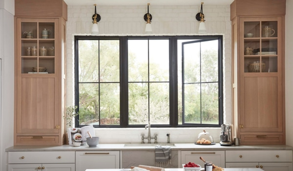 Hinged window combination with black frames and square grilles in a kitchen