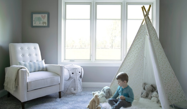 Child plays in bedroom in front of three white, triple-glazed windows