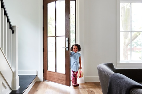 Small child enters a glass front door with multipoint locking system