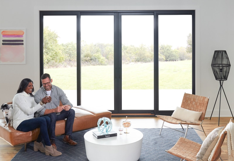 Couple and dog sit in living room in front of patio doors