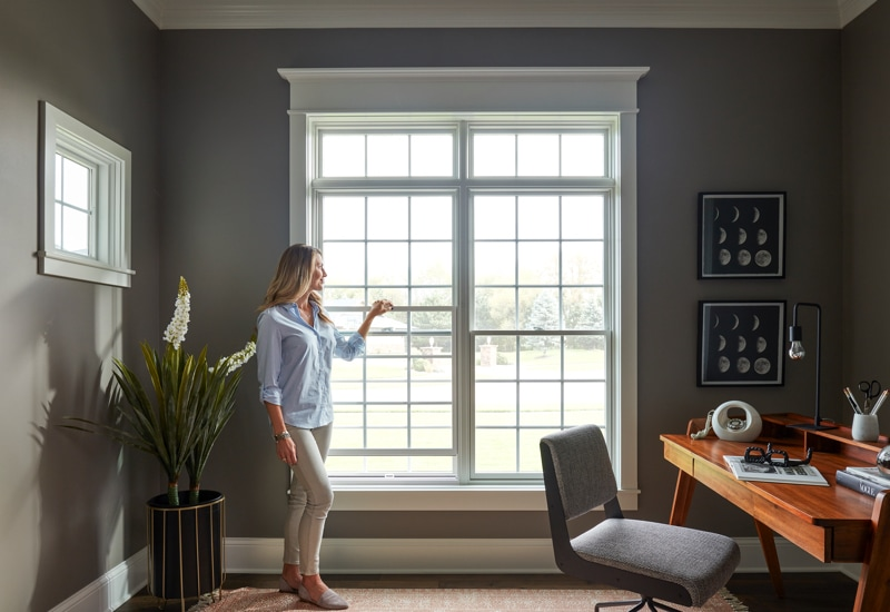 Women looks out energy-efficient Pella windows