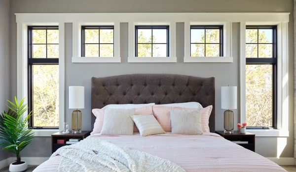 Wall of fiberglass windows framing a bed in a master bedroom