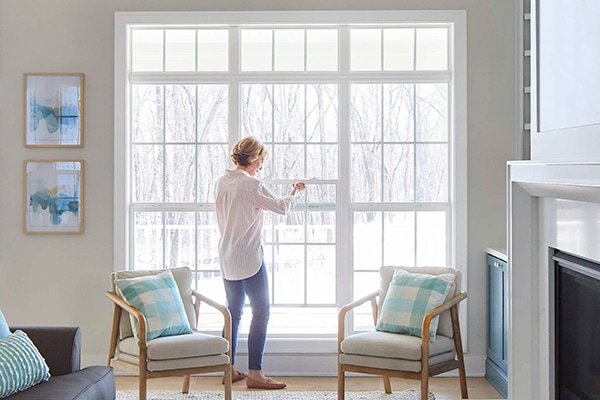 Woman opening up white windows in living room