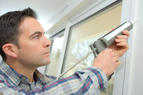 Man caulking windows to repair seal