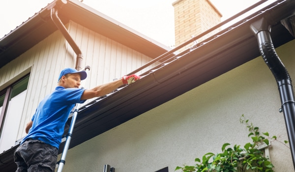 Gutter cleaning professional on ladder clearing debris from gutter