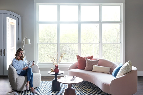 Woman reading a book in living room with Lifestyle Series windows reducing outside noise