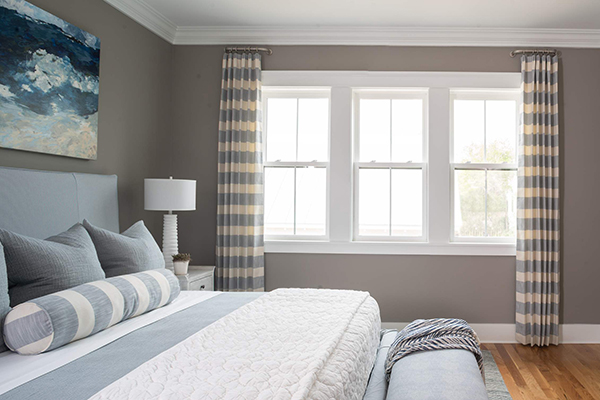 Three white sash windows in a bedroom