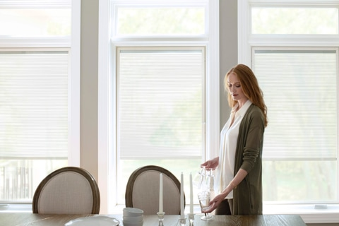 Woman setting dining room table in front of three windows with built-in blinds