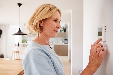 Woman adjusting thermostat to reduce energy costs