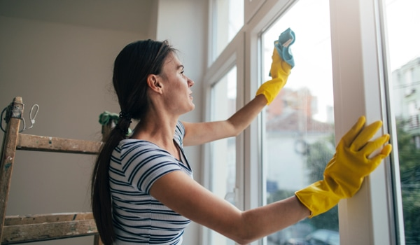 Woman cleans interior of windows with cloth
