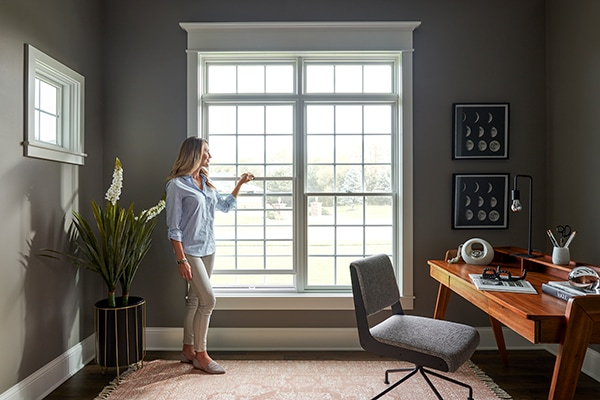 Woman inspecting wood finish of white wood windows