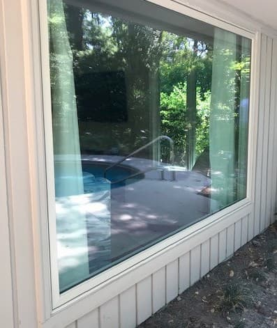 Large wood picture window overlooking hot tub