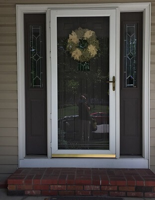old wood entry door with side lights and storm door