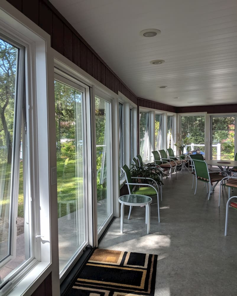 Interior view of porch with a wall of white wood awning windows