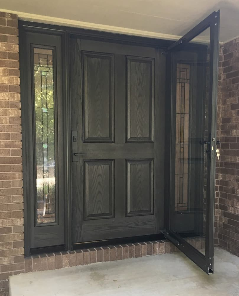 New dark wood-grain fiberglass entry door system with two full-length sidelights and a storm door