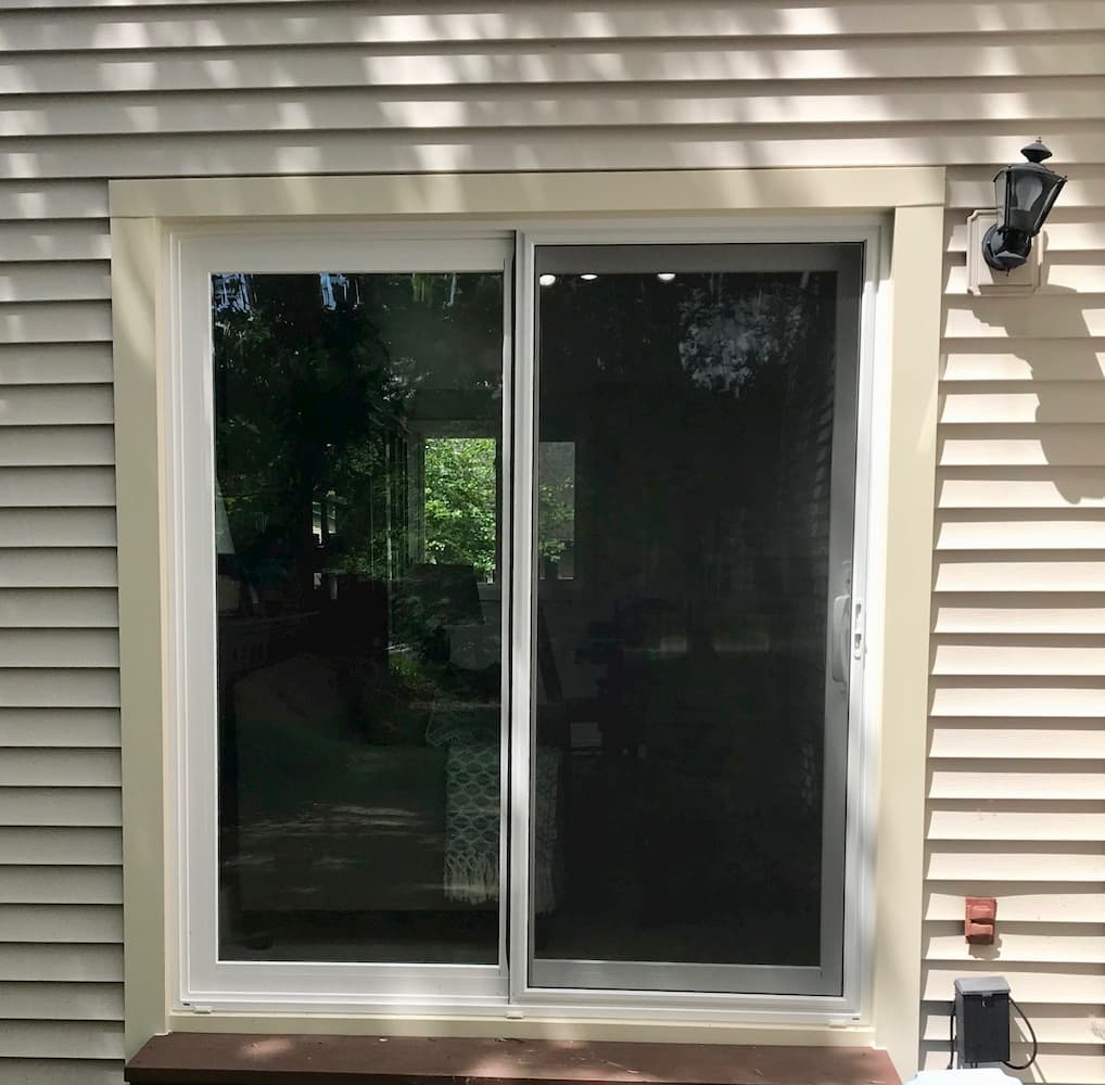 Exterior view of vinyl sliding patio door on home with beige siding