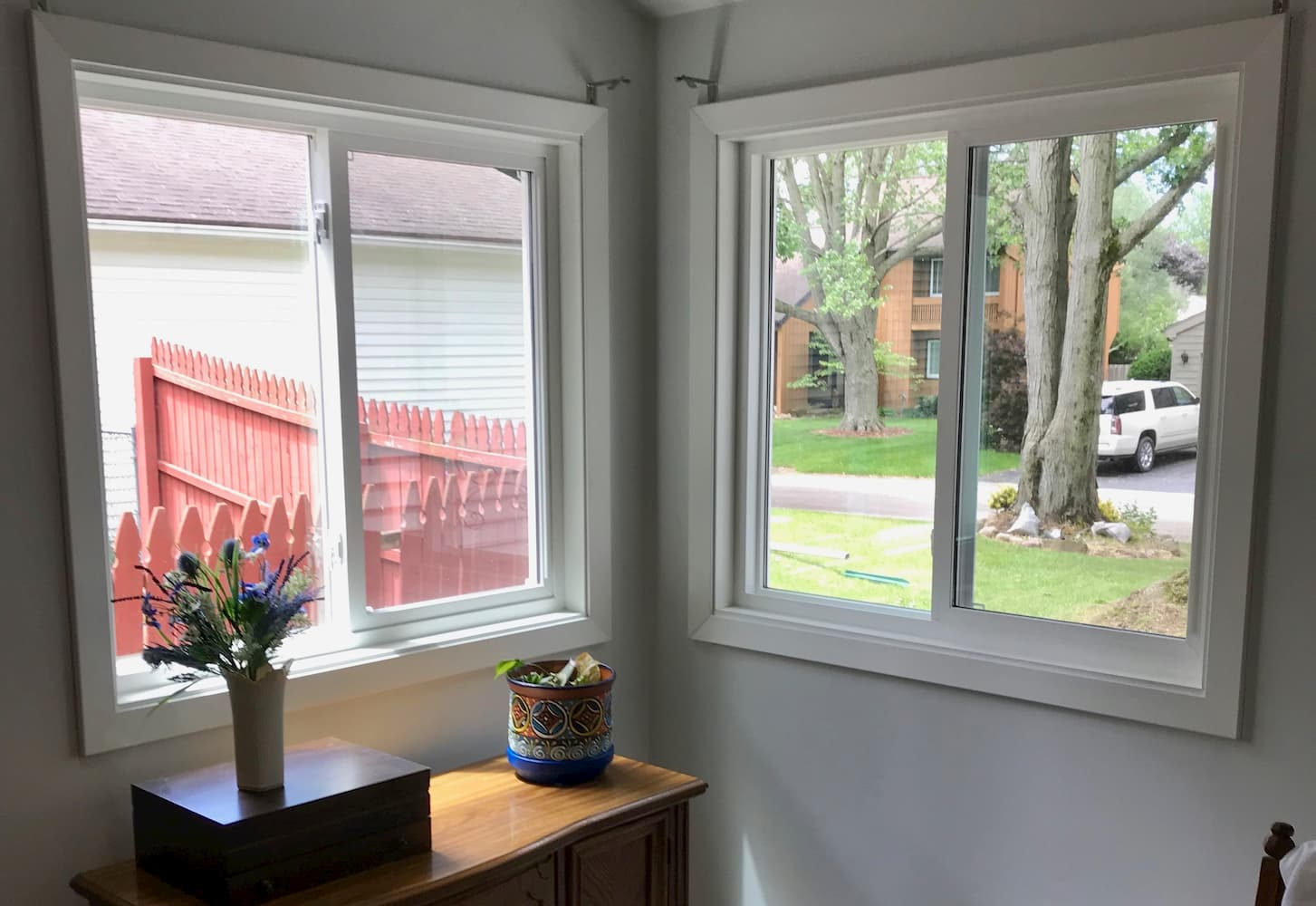 Two sliding vinyl windows in the corner of a bedroom