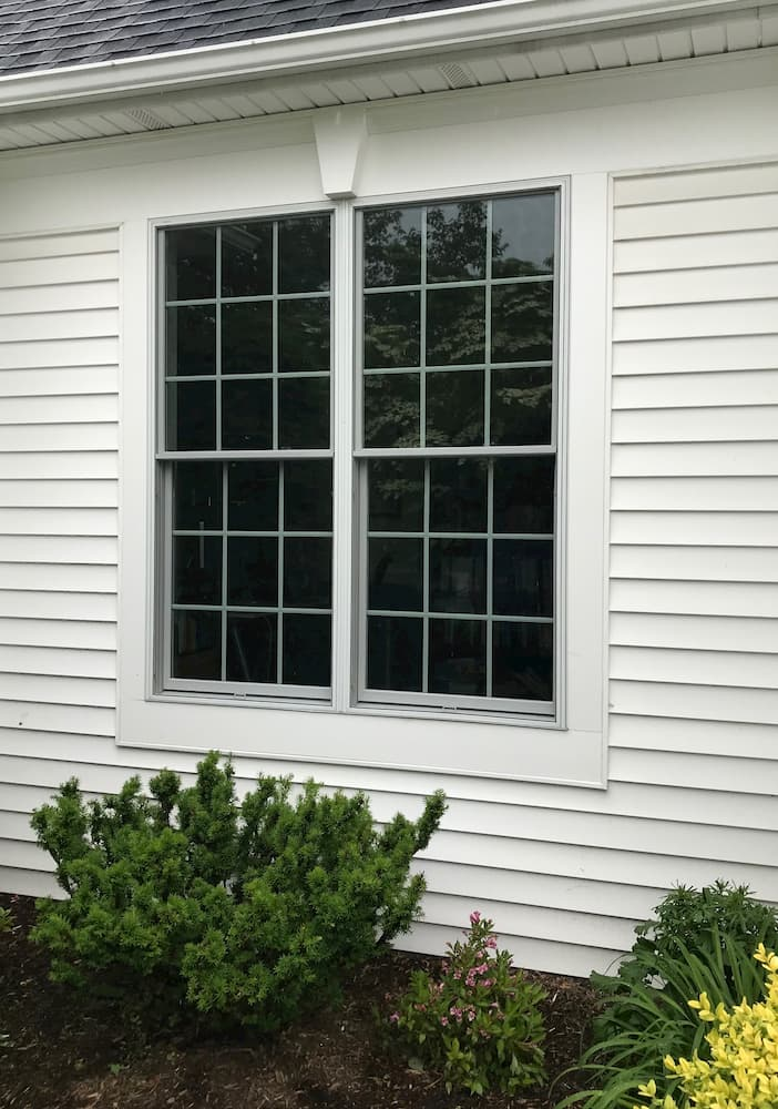 Exterior view of two new double-hung windows on a home with white siding