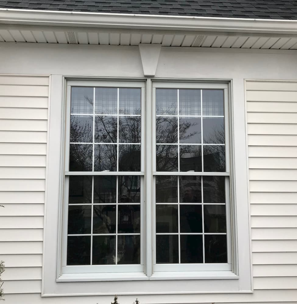 Exterior view of old double-hung windows on house with white siding