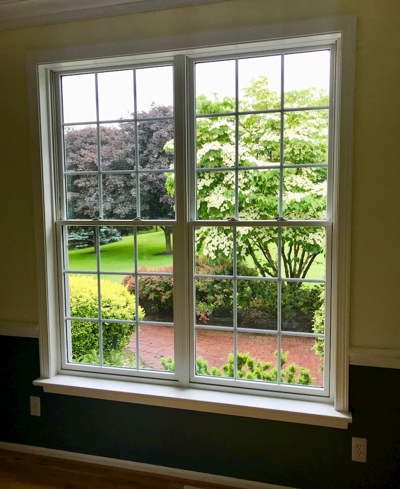 Interior view of two new wood double-hung windows with traditional grille pattern
