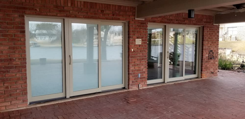 Two clad wood sliding doors on a brick home