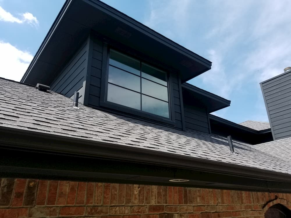 Exterior view of dormer with wood awning window and custom grille pattern