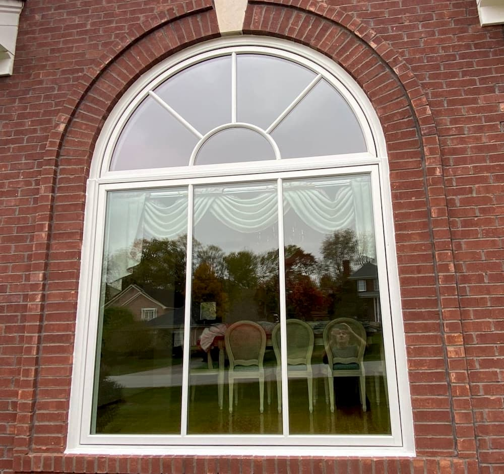 Exterior view of red brick home with new fixed wood window with half circle transom