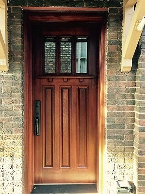 updated wood entry door with decorative shelf and contemporary hardware