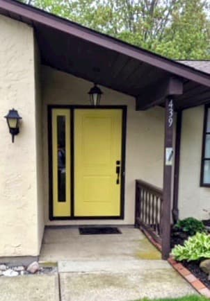 Cheerful yellow fiberglass entry door with full-length sidelight to the left of it