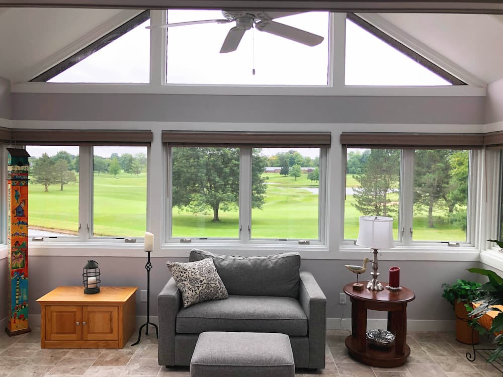 Interior view of four-season room with new white fiberglass casement windows