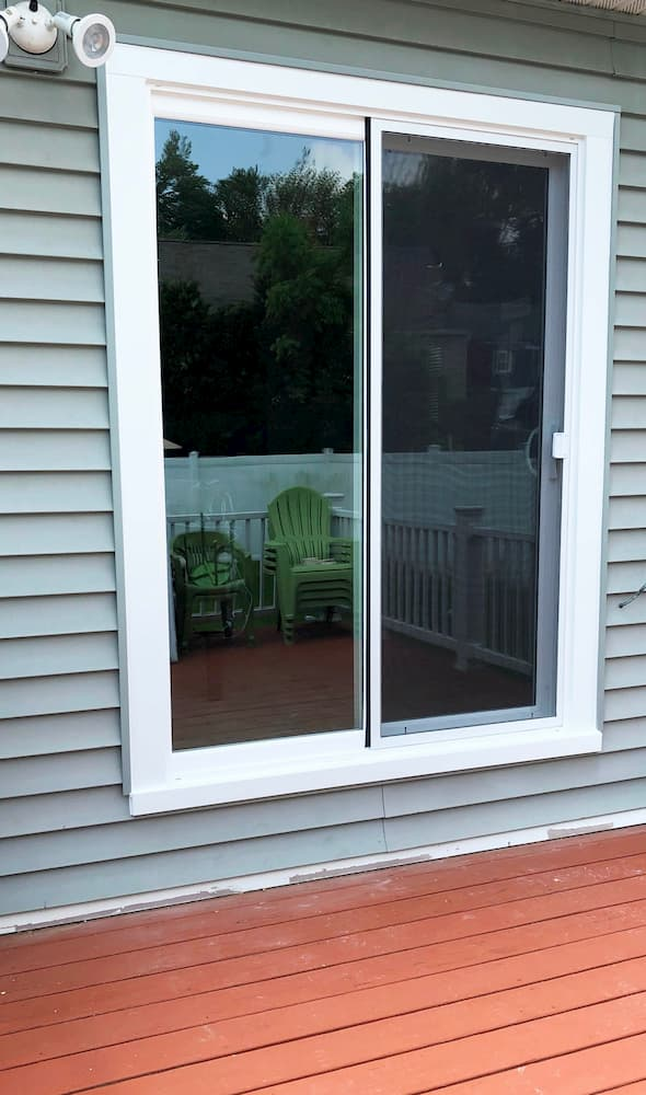 Replacement vinyl sliding patio door on a home with gray siding