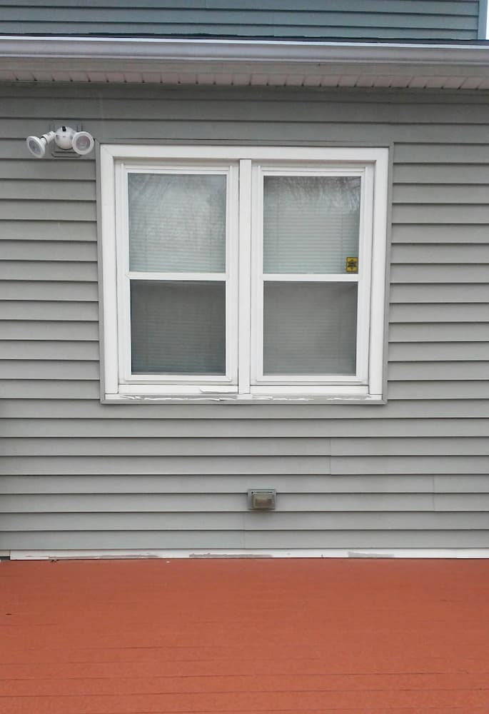 Two double-hung windows on a home with gray siding