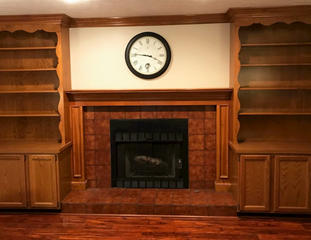 Old-fashioned living room with built-in wood bookcases flanking a fireplace