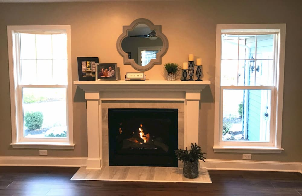 Interior view of two new double-hung windows flanking a fireplace