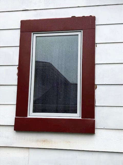 Exterior view of new wood window on home with white siding