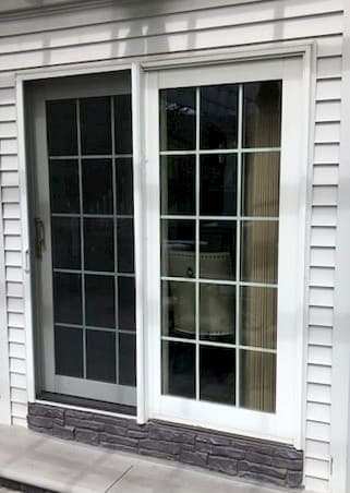Exterior view of old white sliding patio door with traditional grille pattern