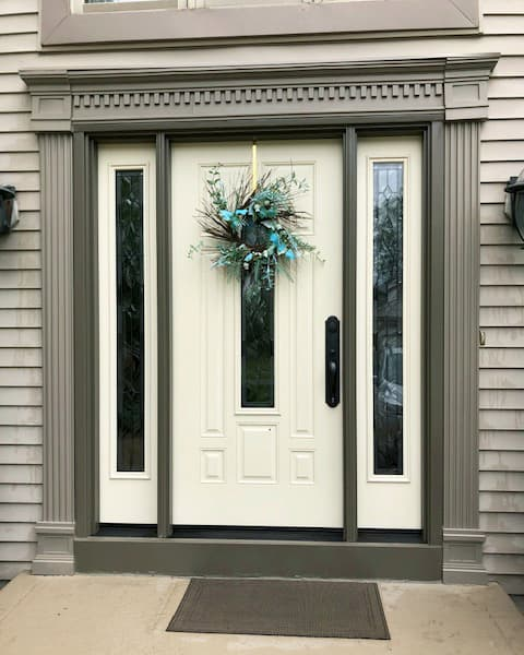 New cream-colored fiberglass entry door framed by two full-length sidelights with statement glass