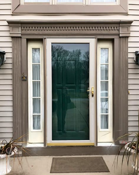 Old entry door with storm door and two full-light sidelights with grilles