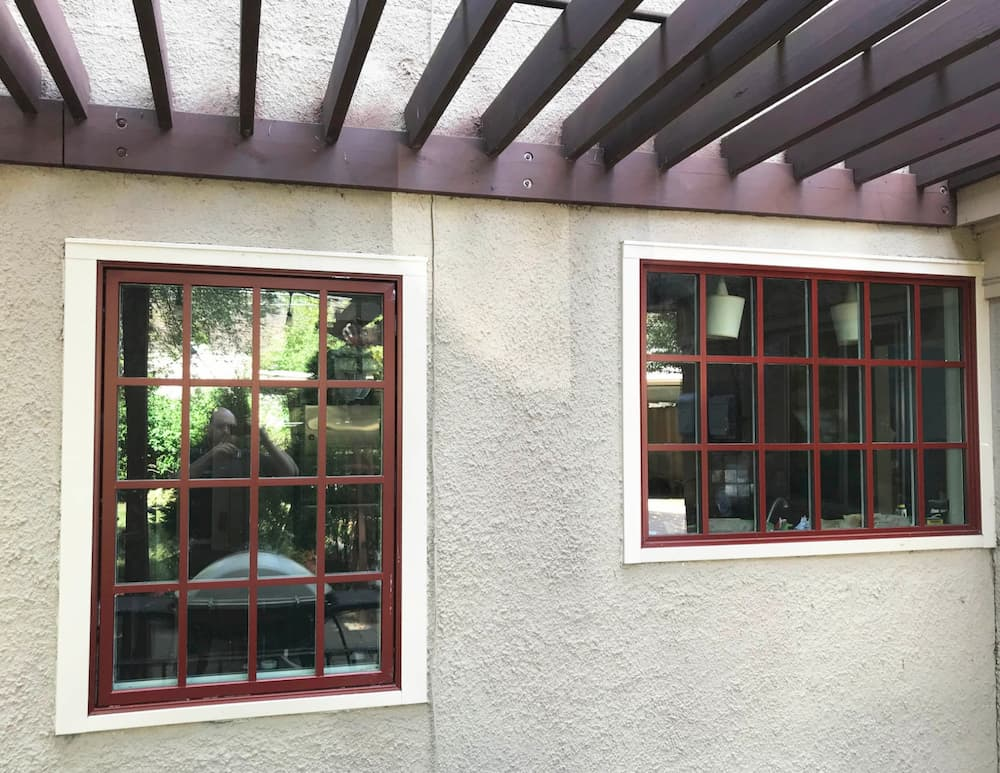 Exterior view of new wood windows with red finish and traditional grille profiles